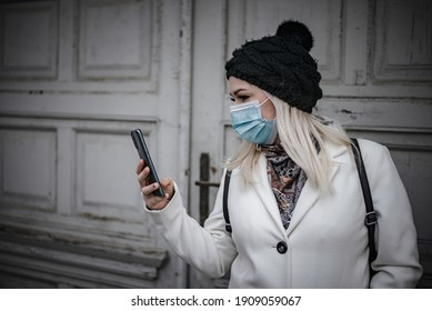 Blonde woman is reading a message while leaving house and wearing face mask