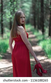 Blonde woman in red dress holding shoes in hand looking over shoulder. Walking on forest path.