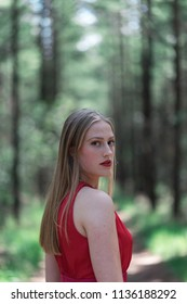 Blonde woman in red in forest looking over shoulder.