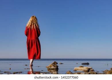 Blonde woman in a red long linen dress standing in the sea in the morning