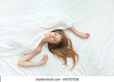 Blonde woman resting in bed at home in the bedroom