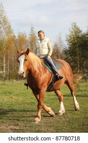 Blonde woman riding chestnut horse without bridle