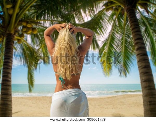 Blonde Woman in sarong standing on the beach