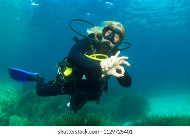 Blonde woman scuba diver underwater gives okay signal