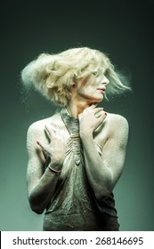 blonde woman shakes out hair from flour. photo with the green filter