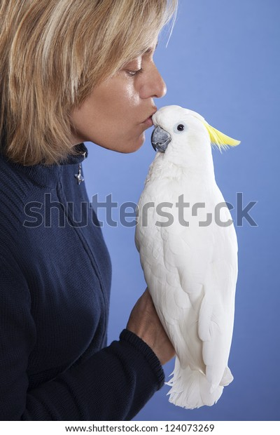 blonde woman showing affection to his white cockatoo