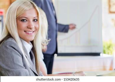 blonde woman sit in business presentation