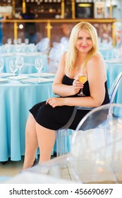 Blonde woman sits at table in ship restaurant and holds wine glass