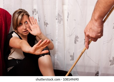 Blonde woman sitting in the corner, looking anxiously at a perpetrator of violence