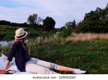 Blonde woman sitting on a blanket outdoors. Picnic time in the nature near river stream. Beautiful summer time evening on the grass. Girl looking on the forest in summer straw hat and trainers.