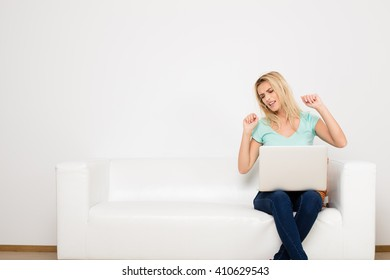 blonde woman sitting on her white sofa with laptop, searching a job