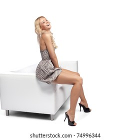 Blonde woman sitting on modern sofa and laughing.