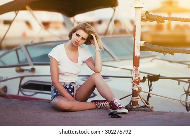 Blonde woman sitting on yachts background and the sea