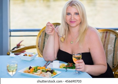 Blonde woman sitting at table in ship restaurant, eating and drinking wine