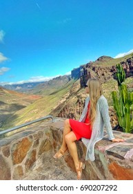 blonde woman sitting at the view point in mountains of gran canaria canary island in spain