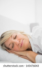 Blonde woman sleeping at home in her bed