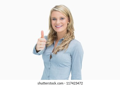 Blonde woman smiling while showing thumbs up