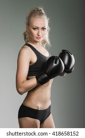 Blonde woman in sportswear and boxing gloves ready to train or attack.