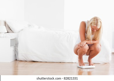 Blonde woman squatting on a weighing machine in her bedroom