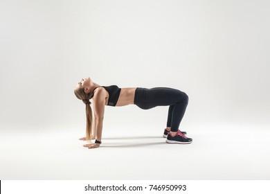Blonde woman standing in flip-the-dog posture. Fitness concept. Indoor shot