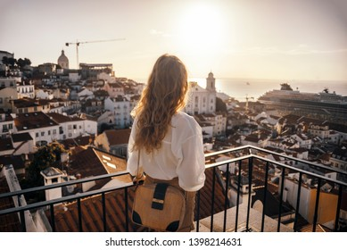 Blonde woman standing on the balcony and looking at coast view of the southern european city with sea during the sunset, wearing hat, cork bag, safari shorts and white shirt