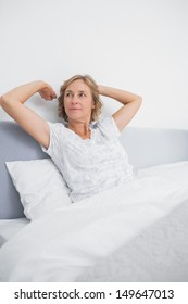 Blonde woman stretching and looking away in bed in the morning in bedroom at home