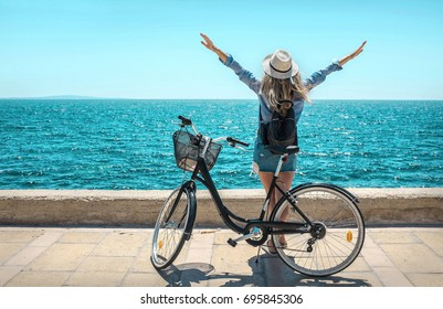Blonde woman in summer hat with her bicycle after walking coastline by the sea beach in sunny summer day under sunlight.