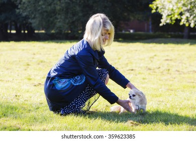 Blonde woman taking care after the dog