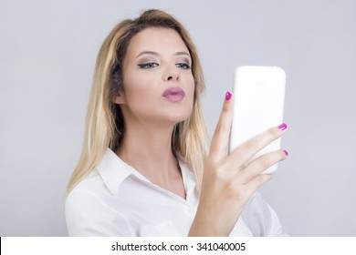 Blonde woman taking a photo of herself on a cell phone