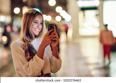 Blonde woman taking photograph with smartphone at night in the street. Defocused city lights at the background. Pretty girl with pigtail hairstyle at night smiling.