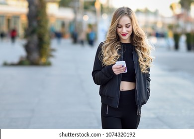 Blonde woman texting with her smart phone in urban background. Beautiful young smiling girl wearing black jacket walking in the street. Pretty russian female with long wavy hair hairstyle.