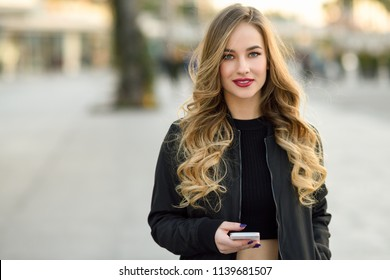 Blonde woman texting with her smart phone in urban background. Beautiful young girl wearing black jacket walking in the street. Pretty russian female with long wavy hair hairstyle.