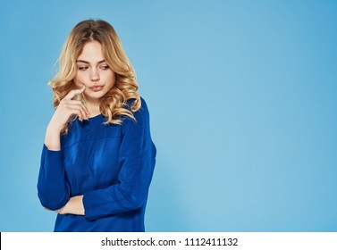 blonde woman thinks on a blue background