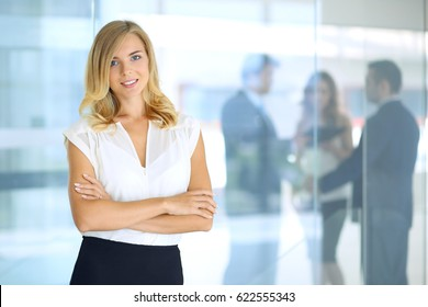 Blonde woman with touch pad computer looking at camera and smiling while business people are shaking hands over office background