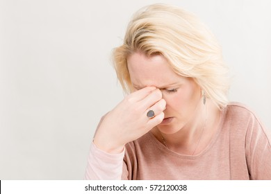 Blonde woman touching the bridge of her nose with eyes closed as if stressed or in pain over a white background with copy space