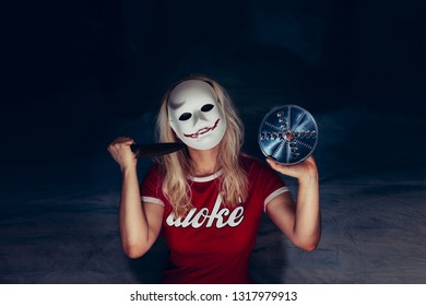 Blonde woman under white mask with spooky bloody smile, holding knife and blade in self defense, horror concept, wearing red t-shirt with white letters saying woke
