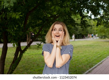 Blonde woman unexpecting meet someone in park. Happy to see old frends.