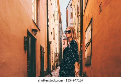 Blonde woman walking in Stockholm  traveling alone fashion lifestyle summer vacations in Sweden old city street