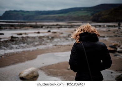 A blonde woman walks on a beach at low tide during the winter on a grey day in the UK