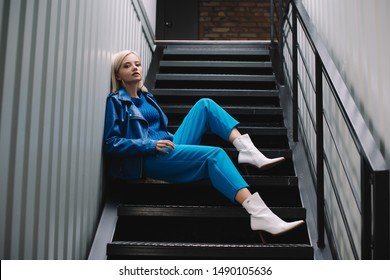 blonde woman wearing blue leather jacket and heels sitting on stairs