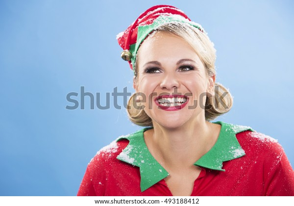 blonde woman wearing elf christmas costume on blue background