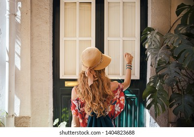 Blonde woman wearing generic red dress and a hat is knocking the door