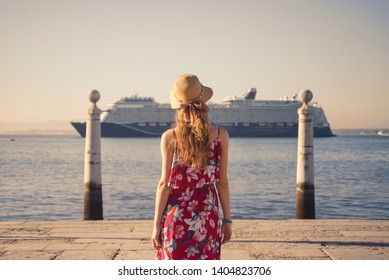 Blonde woman wearing generic red sundress looking at coast and passing touristiccruise ship
