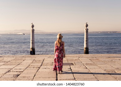 Blonde woman wearing generic red sundress looking at coast in Lisbon
