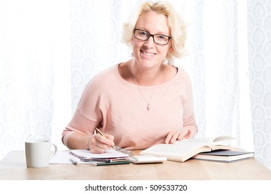A blonde woman wearing glasses dressed in a casual pink top holds a pencil over some work and smiles.  She is sitting at a wooden desk with a mug of tea or coffee and calculator nearby. Copy Space