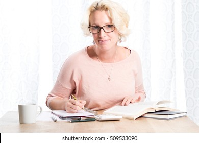 A blonde woman wearing glasses and working at a wooden desk with books, a calculator and writing material smiles to camera. She has a mug of drink and looks relaxed and happy. Copy Space