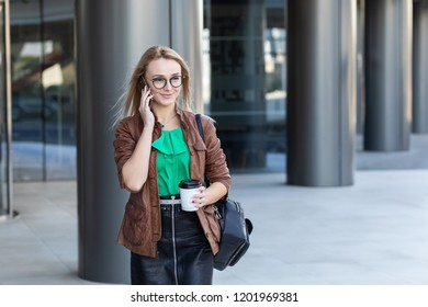 Blonde woman wearing skirt glasses and leather jacket talking on phone, traveling, working in New York City, carrying coffeee, walking on street outside office building