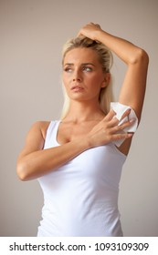 Blonde woman in white shirt wiping the armpit with wet wipes, perspiration, sweat