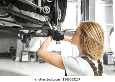 Blonde woman working as mechanic in autoservice, repairing car undercarriage, using wrench. Concentrated girl fixing vehicle in autoservice, with equipment. Automobile lifted on bridge.