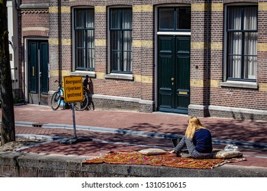 Blonde Woman Working on her Laptop by the Jordaan Canals next to a Sign Saying ''Through Traffic'' in Amsterdam, Netherlands